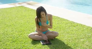 Young woman surfing on a tablet in the sun stock video footage