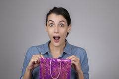 young woman with surprised expression on her face as she open gift bag Royalty Free Stock Photography