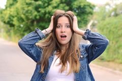 Young woman with surprised expression. Outdoor. Close up portrait of a beautiful young woman with surprised expression looking at camera. Unbelieving, outdoor Royalty Free Stock Images