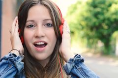 Young woman with surprised expression. Outdoor. Close up portrait of a beautiful young woman with surprised expression looking at camera with headphones Stock Photo