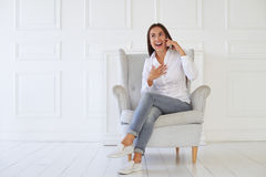 Young woman with surprised expression while talking on the phone. Female in casual outfit sitting against white brick background in the room Royalty Free Stock Photography