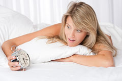 Young woman surprised holding alarm clock. In white bed Stock Image