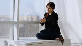 Young woman surprised by a pleasant call phone. Sitting at the window stock video