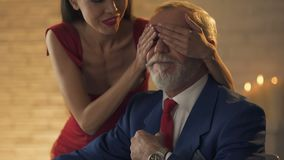 Young woman surprising old man waiting in restaurant, closing eyes, romance