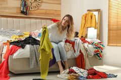 Free Young Woman Surrounded By Different Clothes In Messy Room. Fast Fashion Concept Royalty Free Stock Images - 215258109