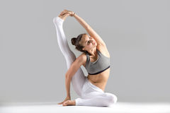 Young woman in Surya Yantrasana pose, grey studio background. Young attractive woman practicing yoga, stretching in Compass exercise, Surya Yantrasana pose Royalty Free Stock Photo