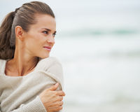Young woman in sweater on beach looking on copy space Stock Image