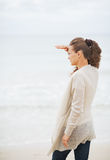 Young woman in sweater on beach looking into distance Stock Image
