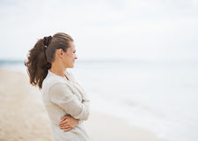 Young woman in sweater on beach looking into distance Royalty Free Stock Images