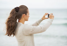 Young woman in sweater on beach taking photo using cell phone Stock Images