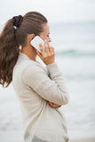 Young woman in sweater on beach talking cell phone Royalty Free Stock Photography