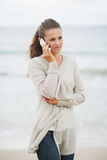Young woman in sweater on beach talking mobile phone Royalty Free Stock Images