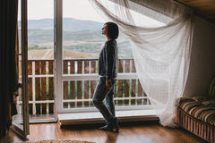 Young woman in a sweater and boyfriend jeans relaxing near big window Stock Images