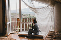 Young woman in a sweater and boyfriend jeans relaxing near big window. With mountains view Stock Photo