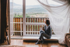 Young woman in a sweater and boyfriend jeans relaxing near big window Royalty Free Stock Photography