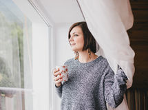 Young woman in a sweater and boyfriend jeans relaxing near big window Stock Photography