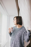 Young woman in a sweater and boyfriend jeans relaxing near big window Royalty Free Stock Images