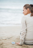 Young woman in sweater with cell phone sitting on lonely beach Royalty Free Stock Photography