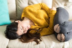 Diarrhea Causing Discomfort And Suffering. Young woman in sweater feeling intense pain in abdomen while lying on sofa royalty free stock photo