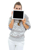 Young woman in sweater hiding behind tablet pc with blank screen Stock Photography