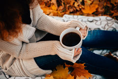Young woman in a sweater and jeans relaxing drink tea on autumn background Stock Photo