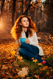 Young woman in a sweater and jeans relaxing drink tea on autumn background Royalty Free Stock Image