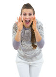 Young woman in sweater shouting through megaphone shaped hands Royalty Free Stock Images