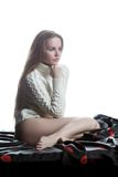 Young woman in sweater sitting on bed Royalty Free Stock Images