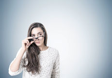 Young woman in sweater taking off glasses, gray Stock Photo