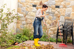 Young woman sweeping autumn leaves veranda. Backyard cleaning pile Stock Image