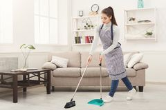 Young woman sweeping house with broom and scoop. Young woman in uniform cleaning house, sweeping floor with broom and scoop, copy space royalty free stock photos