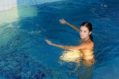 Young woman swimmer in blue pool water Royalty Free Stock Photos