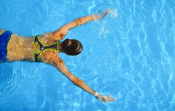 Young woman swimming in a blue water of swimming pool Royalty Free Stock Images