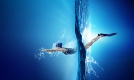 Swimmer in flippers. Mixed media. Young woman swimming in clear blue water. Mixed media stock images
