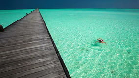Young woman swimming in a coral lagoon next to jetty. Young woman swimming in a coral lagoon next to wooden jetty stock video footage