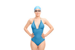 Young woman with swimming goggles. And a blue swimsuit looking at the camera isolated on white background stock photo