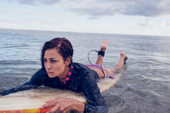 Young woman swimming over surfboard in water Royalty Free Stock Photography