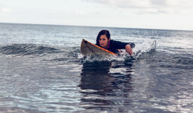 Young woman swimming over surfboard in water Stock Images