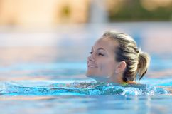 Young woman swimming in the pool Stock Photos