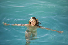 A young woman swimming in a pool royalty free stock image