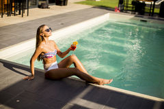 Young woman by the swimming pool with coctail Stock Image