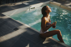 Young woman by the swimming pool with coctail Stock Images