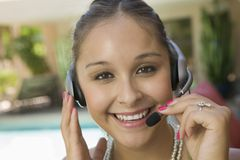 Young woman by swimming pool with headset Royalty Free Stock Photos