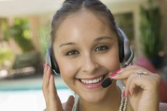 Young woman by swimming pool with headset close up portrait Royalty Free Stock Images