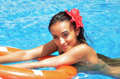 Young woman swimming in a pool with a lifebuoy Royalty Free Stock Photography