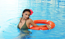 Young woman in a swimming pool with a lifebuoy Stock Photos