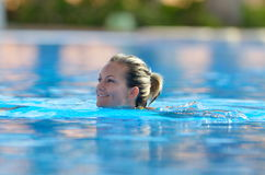 Young woman swimming in the pool on a warm summer day Stock Photo