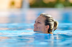 Young woman swimming in the pool on a warm summer day Stock Images