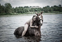 Young woman swimming stallion in in river Royalty Free Stock Photography