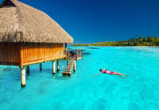 Young woman swimming in tropical lagoon next to overwater villa Stock Image